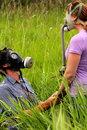 Proposal a young man in love asking for the hand of his girlfriend wearing gas masks in a field of tall grass bad breath allergies Royalty Free Stock Photography