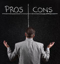 Pros and cons businessman with blackboard list of for against argument concept Stock Photography