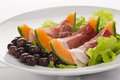 Prosciutto, melon, salad leaf and olives Royalty Free Stock Image