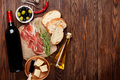 Prosciutto wine olives parmesan and olive oil on wooden table top view with copy space Stock Photos