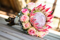 Protea bouquet a king and detailed rose resting on a wooden deck Royalty Free Stock Image
