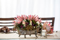 Proteas in silver a detailed centerpiece filled with wild flowers and three vibrant placed on a decorated table with candle Royalty Free Stock Photos