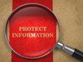 Protect information magnifying glass concept on old paper with red vertical line background Royalty Free Stock Photos