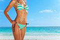 Protect your body with sunscreen close up of young woman standing on the beach in blue striped swim wear and cute drawing of sun Royalty Free Stock Image