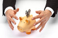 Protect your savings businessman s hands covering piggy bank Stock Image