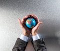 Protecting businessman holding the earth within hands for environment care Royalty Free Stock Photo