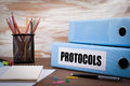Protocols, Office Binder on Wooden Desk. On the table colored pe Royalty Free Stock Photo