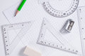 Protractor, rulers, pencil and eraser on squared paper Royalty Free Stock Photo