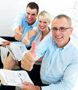 Proud business team giving the thumbs up Stock Image