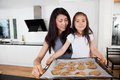 Proud child with raw cookies mother and daughter holding sheet of Royalty Free Stock Photography