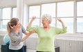 Proud elderly woman flexing her bicep with personal trainer portrait of female looking at women at the rehabilitation center happy Royalty Free Stock Image