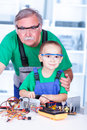 Proud grandfather with grandchild in workshop working on a broken pc power supply Royalty Free Stock Image