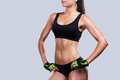 Proud of her perfect body close up young sporty woman with holding hands on hip while standing against grey background Stock Photos