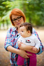 Proud mom holding baby outdoors in a park Royalty Free Stock Image