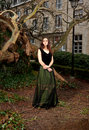 Proud woman in victorian outfit in the park girl a green dress front of a house and trunks of trees Royalty Free Stock Images
