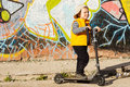 Proud young boy with his scooter posing sideways in front of an old wall covered in colourful graffiti Royalty Free Stock Image