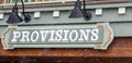 Provisions sign in the falling snow front of a shop for selling all types of items that might be needed a trip to mountains red Stock Image