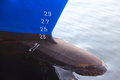 Prow of large sea going boat detail the ship painted blue and black with depth markers in white painted on the hull Stock Photo