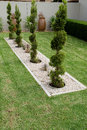 Pruned conifer shrubs in a small rectangular pebble garden surrounded by lawn Stock Photo