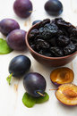Prunes with fresh plums on a wooden background Royalty Free Stock Photos