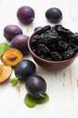 Prunes with fresh plums on a wooden background Royalty Free Stock Images