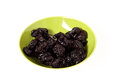 Prunes a pile of on a bowl isolated Royalty Free Stock Images
