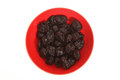 Prunes a pile of on a bowl isolated Royalty Free Stock Image