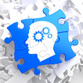 Psychological concept on blue puzzle profile of head with cogwheel gear mechanism located Stock Images