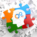 Psychological concept on multicolor puzzle profile of head with cogwheel gear mechanism located Stock Photos