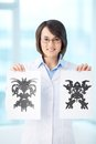 Psychological test vertical portrait of a charming psychologist showing two pictures of rorschach Stock Photo