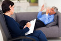 Psychologist with patient middle aged female making note while talking Royalty Free Stock Photos