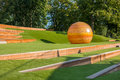 Public city park with long benches and wooden globe modern design. Royalty Free Stock Photo