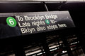 Public new york city subway sign pointing to brooklyn bridge Stock Images