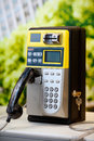 Public phone in expo a yellow and black Royalty Free Stock Photography
