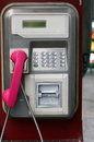 Public phone machine with pink receiver in the street Stock Images
