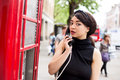 Public phone young woman using a Royalty Free Stock Photography