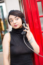 Public phone young woman using a box Royalty Free Stock Image