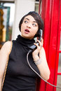 Public phone young woman using a box Royalty Free Stock Photo
