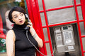 Public phone young woman using a in london Stock Image