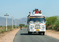 Public transport bus drives with plenty of passengers on roof rajasthan india circa february the driving the road Royalty Free Stock Photos