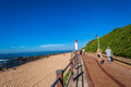 Public walkway lighthouse beach ocean promenade at umhlanga rocks with distant popular tourism destination town just outside Stock Photography