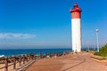 Public walkway lighthouse beach ocean promenade at umhlanga rocks with distant popular tourism destination town just outside Royalty Free Stock Image