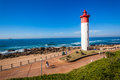 Public walkway lighthouse beach ocean promenade at umhlanga rocks with distant popular tourism destination town just outside Royalty Free Stock Photography
