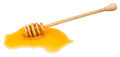 Puddle of clear honey and wooden spoon isolated Royalty Free Stock Photo
