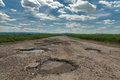 Puddle on old cracked road Royalty Free Stock Photo