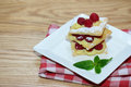 Puff pastry cake with mint leaves and raspberries in a white plate, background with copy space Royalty Free Stock Photo