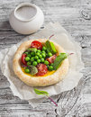 Puff pastry egg tartlet with fresh green peas and cherry tomatoes on wooden rustic board.