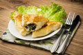 Puff pastry with spinach and feta (triangles) on the wooden background.