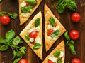 Puff pizzas with mozzarella cheese cherry tomatoes and baby basil viewed from above Stock Images
