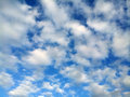 Puffy clouds perfectly spaced white on an intense blue sky Stock Photography
